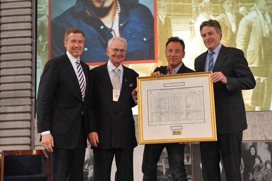 Tom Strickland presenting an award to Bruce Springsteen, Brian Williams and Peter Peterson at 2010 Ellis Island Family Heritage Awards